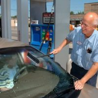 Venema Service Inc. owner John Venema washes a customer's windshield while filling her car fuel tank with gas. Venema's Zeeland gas station is one of the few full serve stations in the state. (Mark Copier | The Grand Rapids Press)